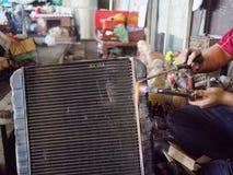Yrkesmässig arbetare med gas som löder att kyla för element av bilen i garageseminarium royaltyfria foton