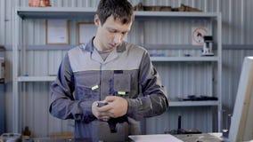 Yrkesmässig arbetare som använder den speciala apparaten för metalldelar inomhus lager videofilmer