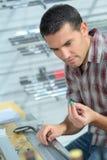 Yrkesmässig arbetare som arbetar på maskinen på gitarrseminariet royaltyfri foto