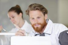 Yrkesmässig arbetare som målar försiktigt objekt med vit målarfärg fotografering för bildbyråer