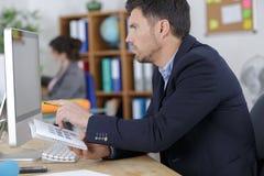 Yrkesmässig arbetare som ser datorskärmen arkivfoton