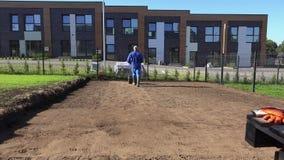 Yrkesmässig arbetarman som pressar samman jordning efter gräsmatta som kärnar ur suggan Statisk elektricitetskott arkivfilmer