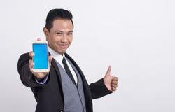Yrkesmässig asiatisk affärsman som visar en mobiltelefon och gör upp tummar fotografering för bildbyråer