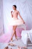 Yrkesmässig balettdansör som poserar på rosa färger arkivfoto
