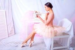 Yrkesmässig balettdansör som ser i spegeln på rosa färger arkivbilder