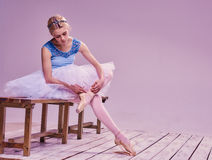 Yrkesmässig ballerina som sätter på hennes balettskor royaltyfria foton