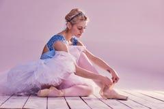 Yrkesmässig ballerina som sätter på hennes balettskor Royaltyfri Bild