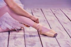 Yrkesmässig ballerina som sätter på hennes balettskor arkivbilder