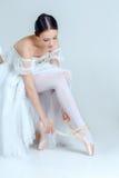 Yrkesmässig ballerina som sätter på hennes balettskor arkivfoton