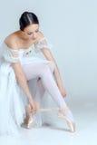 Yrkesmässig ballerina som sätter på hennes balettskor arkivbild