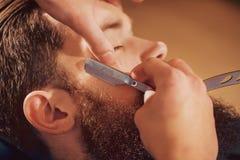 Yrkesmässig barberare som rakar skägget av hans klient royaltyfri fotografi