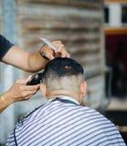 Yrkesmässig barberare som utformar hår som mottar frisyr genom att använda hårcu arkivbild