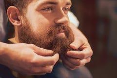Yrkesmässig barberare som utformar skägget av hans klient Royaltyfri Bild