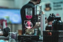 Yrkesmässig barista som gör spetial sund utslagsplats läckert te i stång från hallonbär royaltyfri foto