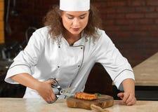 Yrkesmässig biff för kockklipphöna med sax Arkivbilder