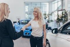 Yrkesmässig bilåterförsäljare som hjälper hennes kvinnliga kund arkivfoton