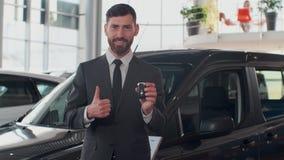 Yrkesmässig bilförsäljare som ler rymma lyckligt biltangenter som framme står av nya bilar på återförsäljaren lager videofilmer
