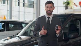 Yrkesmässig bilförsäljare som ler rymma lyckligt biltangenter som framme står av nya bilar på återförsäljaren arkivfilmer