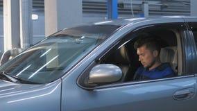 Yrkesmässig bilmekaniker som arbetar i modern service för auto reparation och kontrollerar motorn arkivfilmer