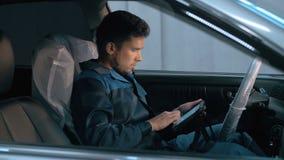 Yrkesmässig bilmekaniker som arbetar i modern service för auto reparation och kontrollerar motorn stock video