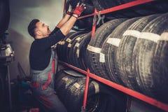Yrkesmässig bilmekaniker som väljer det nya gummihjulet i service för auto reparation fotografering för bildbyråer