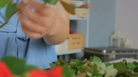 Yrkesmässig blomsterhandlare som arbetar med blommor på studion arkivfilmer