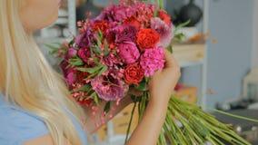 Yrkesmässig blomsterhandlare som gör blom- bröllopsammansättning på blomsterhandeln stock video