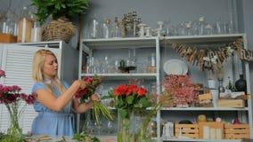 Yrkesmässig blomsterhandlare som gör den härliga buketten på blommalagret arkivfilmer
