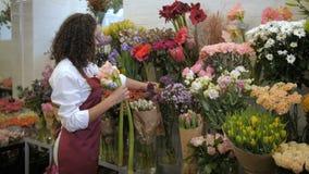 Yrkesmässig blomsterhandlare som väljer blommor för bukett stock video