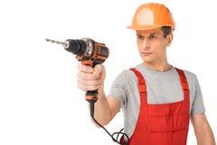 Yrkesmässig byggmästare i overaller och hardhatinnehavdrillborr royaltyfri fotografi