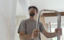 Yrkesmässig byggnadsarbetare som gör en hem- makeover royaltyfri fotografi