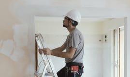 Yrkesmässig byggnadsarbetare som gör en hem- makeover fotografering för bildbyråer