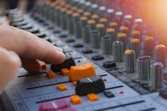 Yrkesmässig closeup för solid blandare för etapp på handen för solid tekniker genom att använda den ljudsignal blandningglidaren Royaltyfri Foto