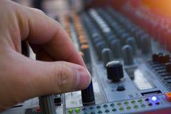 Yrkesmässig closeup för solid blandare för etapp på handen för solid tekniker genom att använda den ljudsignal blandningglidaren Arkivfoto