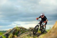 Yrkesmässig cyklist som rider cykeln på Rocky Trail extrem sport Royaltyfria Bilder