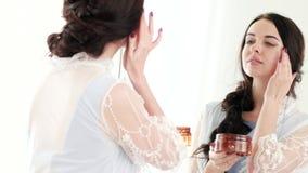Yrkesmässig daglig kräm för hudomsorg för unga damer, hållande orange krus för kvinna av kräm stock video