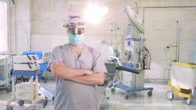 Yrkesmässig doktorsstående Den manliga doktorn med ett specialt undersökninginstrument på hans huvud står i ett operationrum arkivfilmer