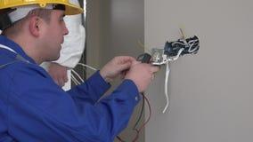 Yrkesmässig elektrikerman som använder det speciala hjälpmedlet för att kontrollera spänning för vägghålighet stock video