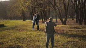 Yrkesmässig fotograf som fotograferar barn som älskar par på naturen i parkera stock video