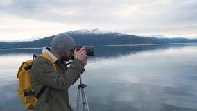 Yrkesmässig fotografman som tar fotografiet av dalen med den bärande ryggsäcken för DSLR som fotograferar sceniskt landskap lager videofilmer