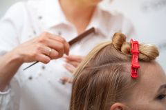 Yrkesmässig frisör som gör en frisyr till en blond modell arkivfoton