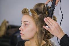 Yrkesmässig frisör som gör frisyren för ung nätt kvinna - danande krullar arkivfoton