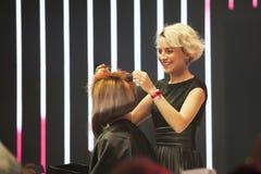 Yrkesmässig frisör som gör stilfull frisyr på en etapp royaltyfria bilder
