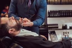 Yrkesmässig frisör som modellerar skägget med sax och hårkammen på frisersalongen Arkivbild