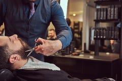 Yrkesmässig frisör som modellerar skägget med sax och hårkammen på frisersalongen Arkivfoto