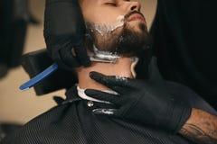 Yrkesmässig frisör som rakar klienten med den raka rakkniven royaltyfri foto