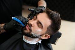 Yrkesmässig frisör som rakar klienten med den raka rakkniven arkivfoton