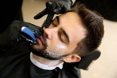 Yrkesmässig frisör som rakar klienten med den raka rakkniven royaltyfria foton