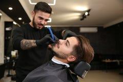 Yrkesmässig frisör som rakar klienten med den raka rakkniven royaltyfria bilder