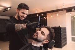 Yrkesmässig frisör som rakar klienten med den raka rakkniven fotografering för bildbyråer